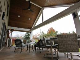 wood patio ceiling with recessed lighting and fan
