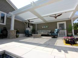 All white outdoor louvered roof system with overhead lighting and fans