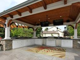 large outdoor kitchen with flat screen televisions