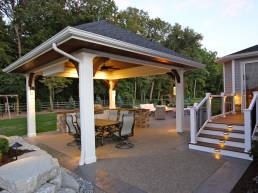covered patio with ambient lighting and stone counter tops