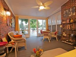 Brick porch with white furniture leading onto deck