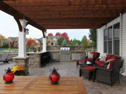 covered stone patio with dark wood pergola