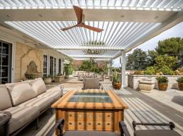 large outdoor struxure with louvered roof and fans