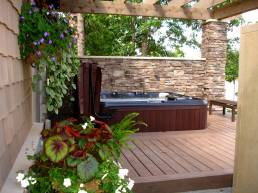 outdoor hot tub on deck with stone privacy wall