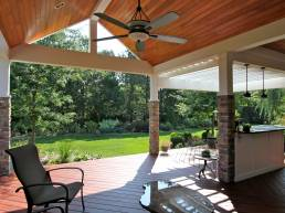 light wood plank ceiling covered deck with brick columns